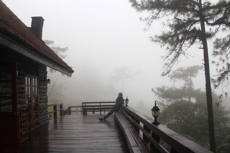 Architecture Beauty In Nature Building Exterior Built Structure Day Fog Foggy Footbridge Full Length Jetty Mist Nature One Person Outdoors Pier Railing Real People Scenics Sky Tranquil Scene Tranquility Tree Water Weather Wood - Material