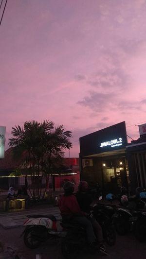 People on illuminated street against sky at dusk