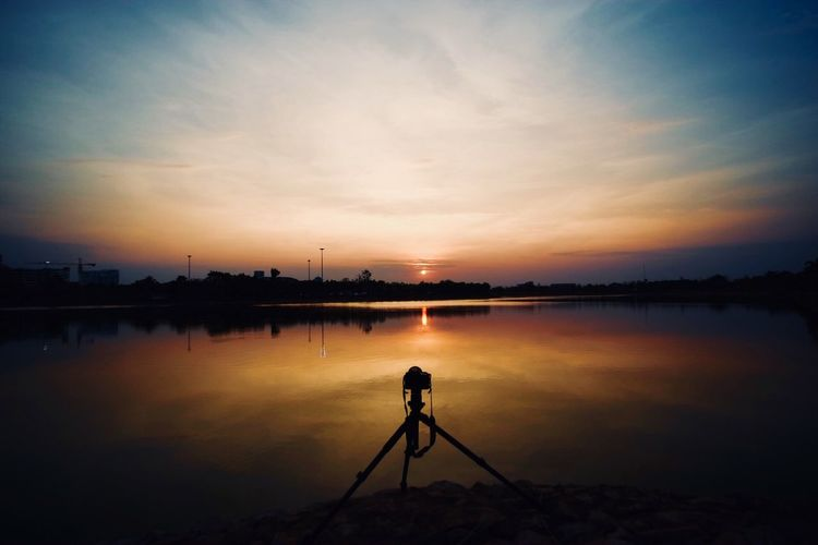 แสงสุดท้าย Sunset Tranquility Sky Reflection Silhouette Beauty In Nature Tranquil Scene Real People One Person Full Length Water Nature Camera - Photographic Equipment Scenics Standing Outdoors Lake Photography Themes Photographing People