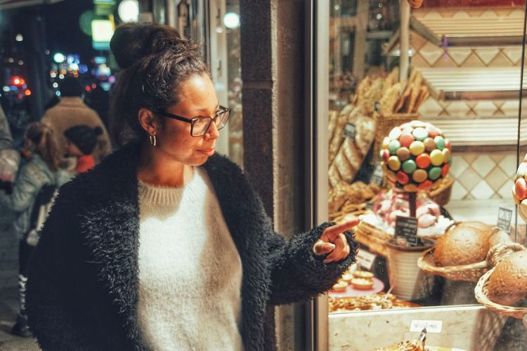Woman looking though store window in city at night