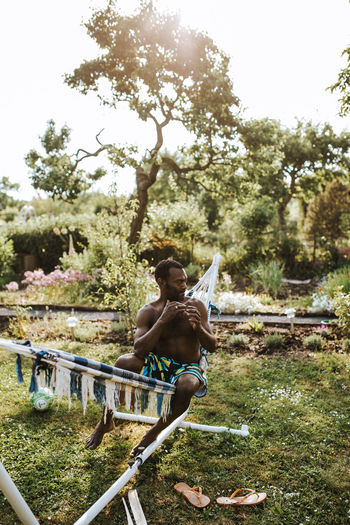 Shirtless man relaxing on hammock in yard