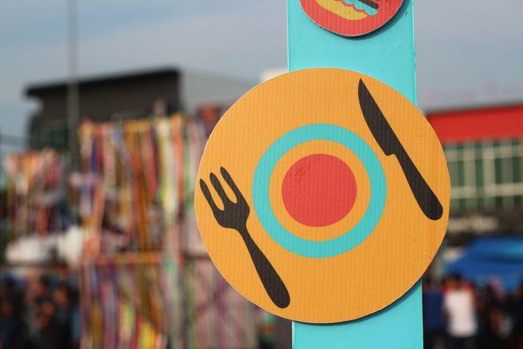 Close-up of restaurant symbol hanging outdoors