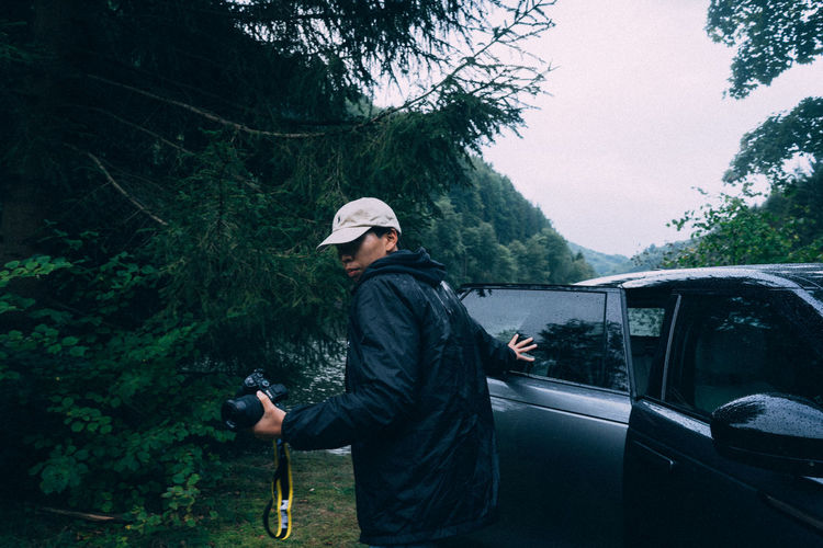 Full length of man standing on road in forest