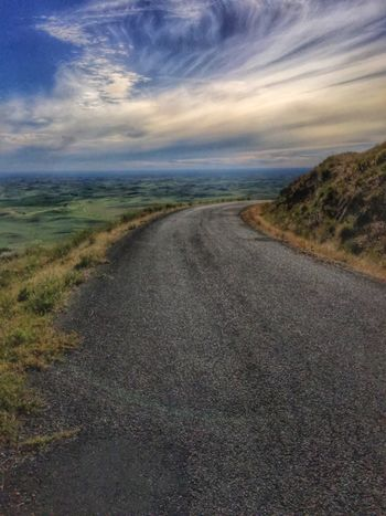Open road winding around mountain with rolling hills in background in Palouse  The Palouse