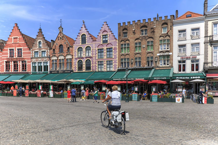 Bruges, Belgium - July 7, 2017: Woman riding a bike in the Market Square of Bruges with the iconic colored buildings on background Beer Belgium Brugge Chocolate Dijver Canal Duvel Flanders Panoramic View Provinciaal Hof West Flanders Aerial View Belfry Tower Bikes Bruges Europe Flower French Fries Holland Market Square Medieval Town Mussels