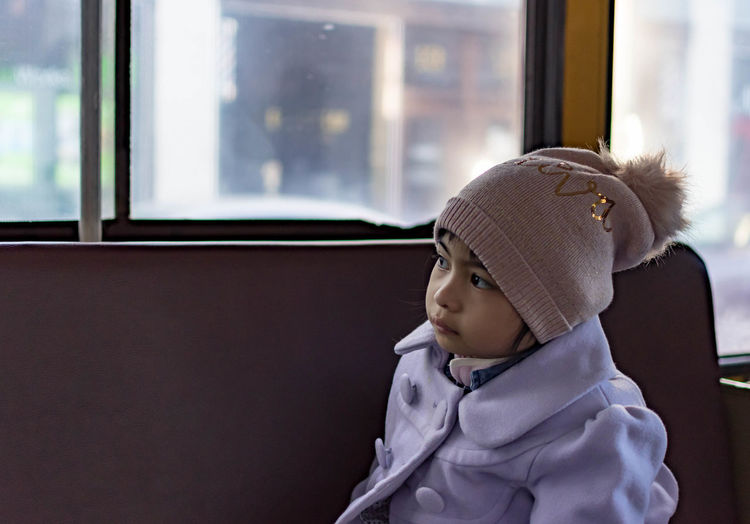 Cute girl sitting in bus while looking away