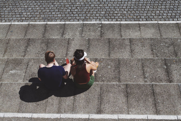High angle view of friends sitting on staircase