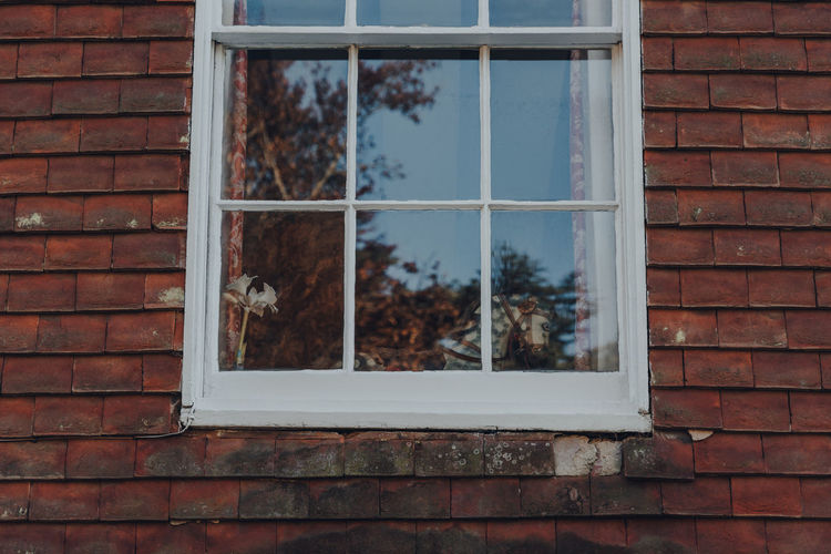 Rocking horse by the window of a house in rye, east sussex, uk.