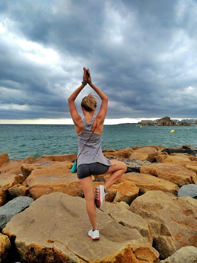 Rear view of woman doing yoga while standing on rock at beach against sky
