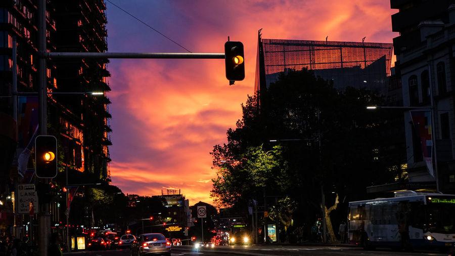 Illuminated road signal in city against orange sky