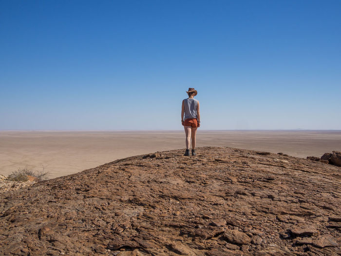 Rear View Of Young Woman Standing On Desert Rock Against Clear Blue Sky, Namib Naukluft National Park, Namibia