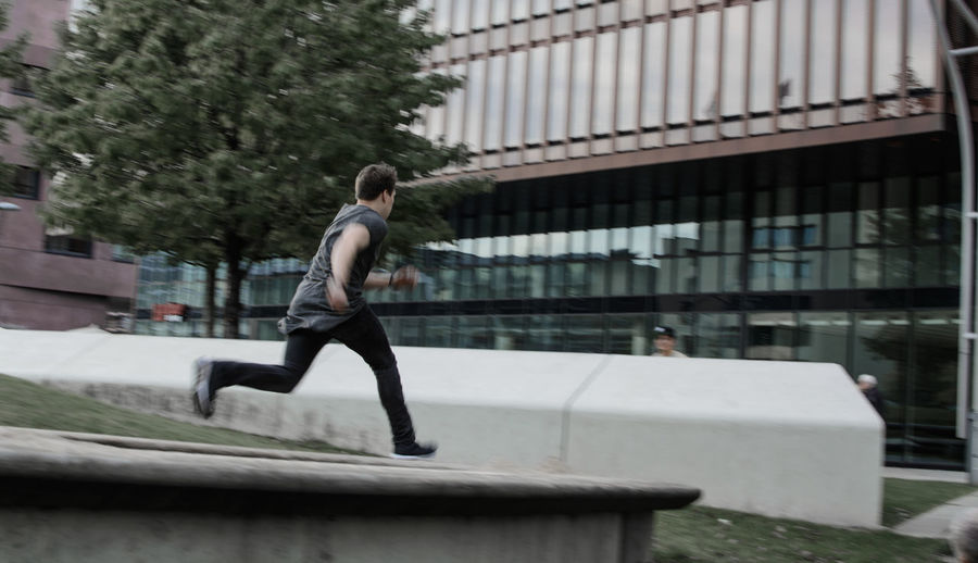 Side view of man running in city