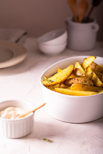 Delicious slices of baked potatoes with rosemary and oil in a ceramic bowl