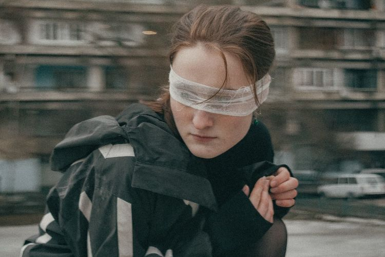Close-up of woman with blindfold standing against building