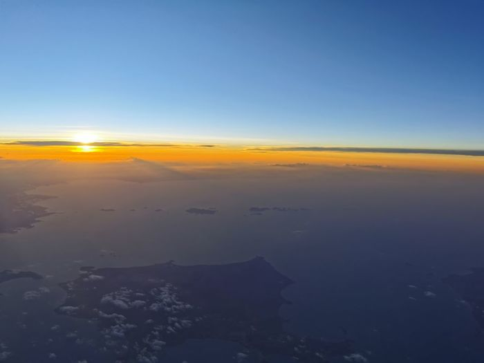 Aerial view of landscape against sunset sky