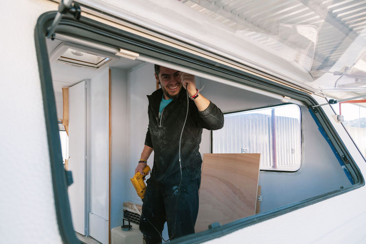 Portrait of smiling man holding drill seen through window of camper trailer