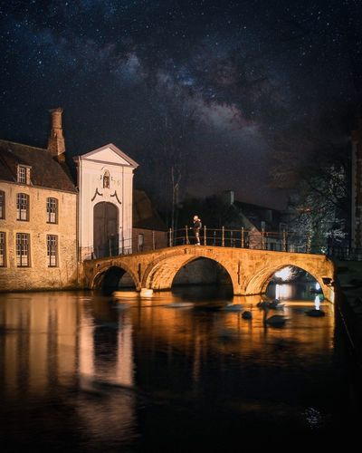 Arch bridge over river by buildings against sky at night
