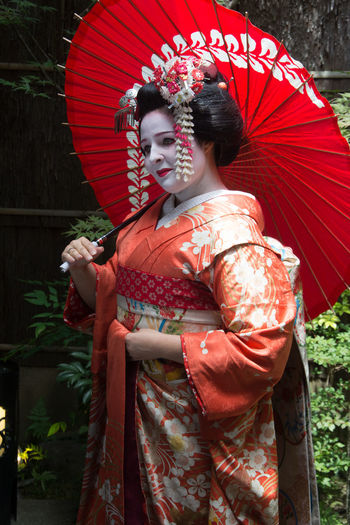 Woman Wearing Kimono Holding Red Umbrella While Standing Outdoors