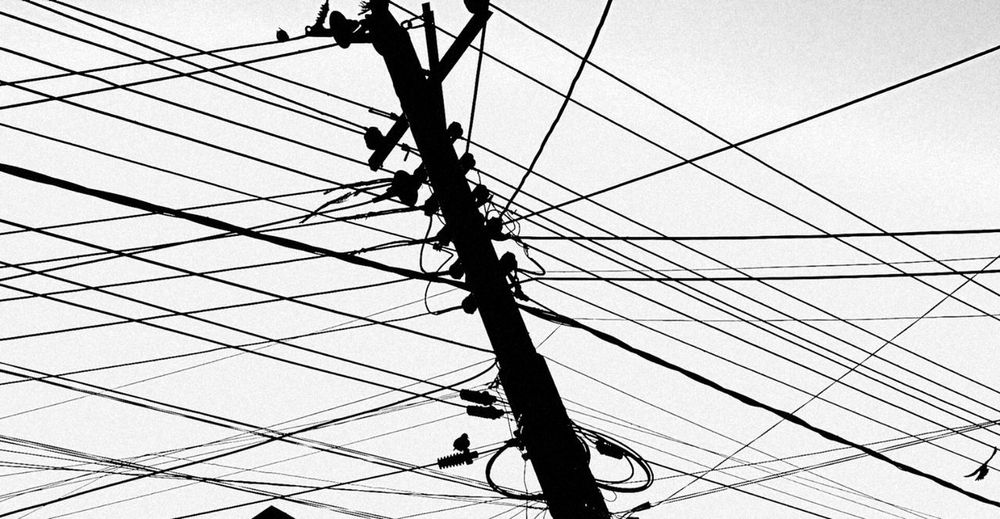 Low angle view of power lines against clear sky