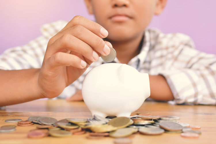 Midsection of boy putting coins in piggy bank at wooden table against pink background