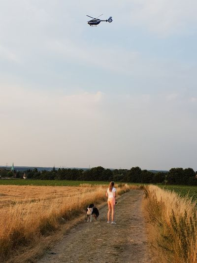 Full Length Of Girl Standing With Dog On Dirt Road During Sunset
