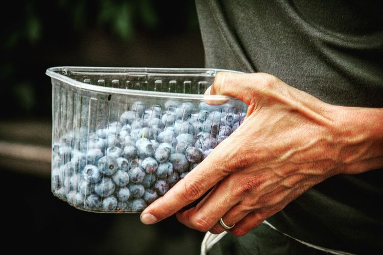 Cropped image of person carrying blueberries in plastic container
