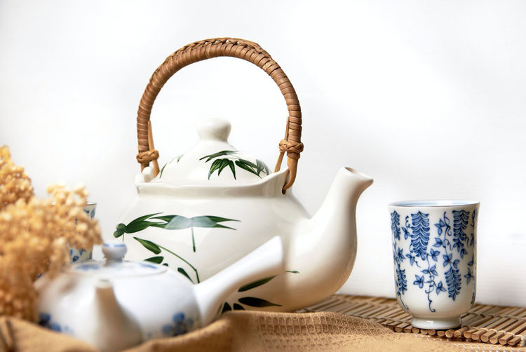 Close-up of tea cup on table against white background