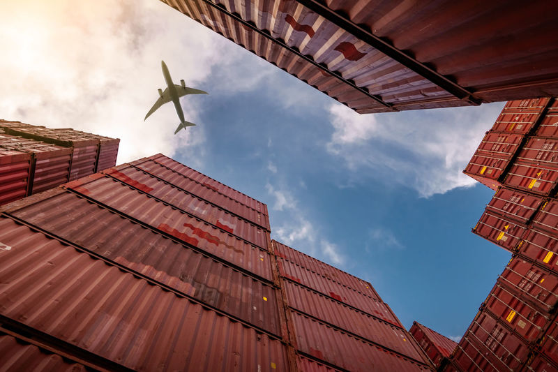 Airplane flying above container logistic. cargo and shipping business. container ship for export.