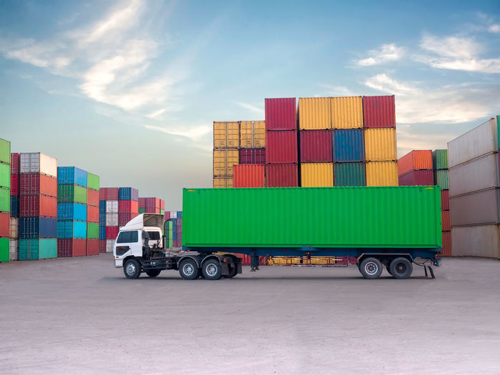 Truck with cargo containers at commercial dock against sky