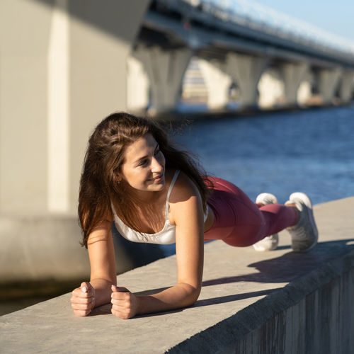 Full length of beautiful young woman exercising by sea against bridge