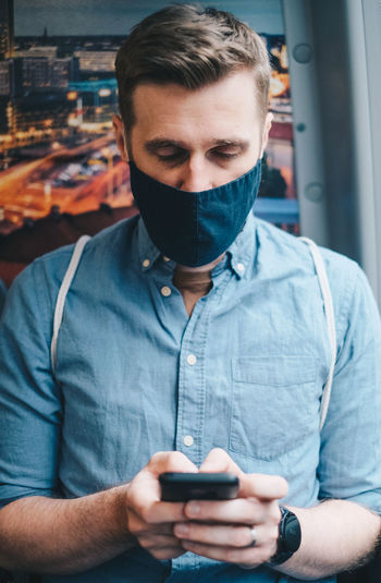 Close-up of mid adult man wearing mask using smart phone while sitting in bus