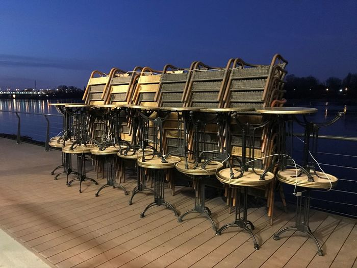 Chairs and tables in sea against clear sky