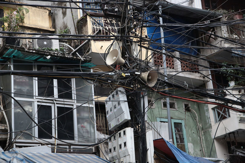 Low angle view of tangled on cables on pole against building