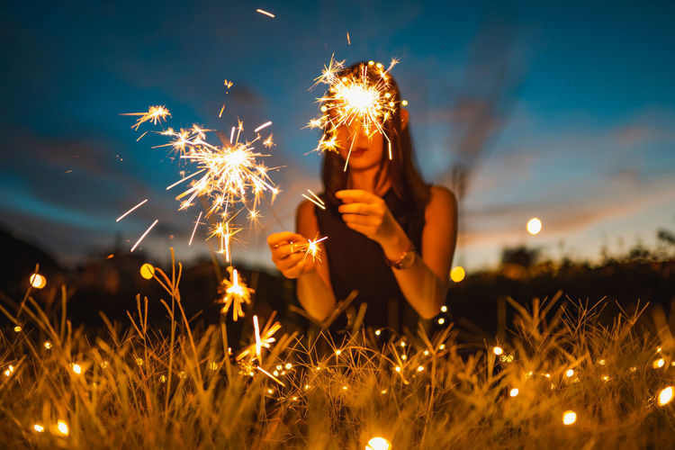 Woman with illuminated sparklers sitting on grass during sunset