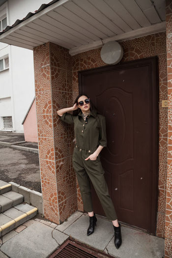 Full length front view portrait of tall slim brunette in green suit in urban setting, fashion
