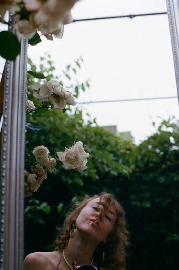 Portrait of woman holding flowering plants