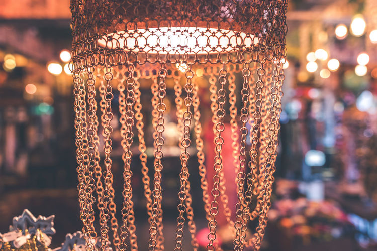 Close-up of illuminated lighting equipment hanging at night