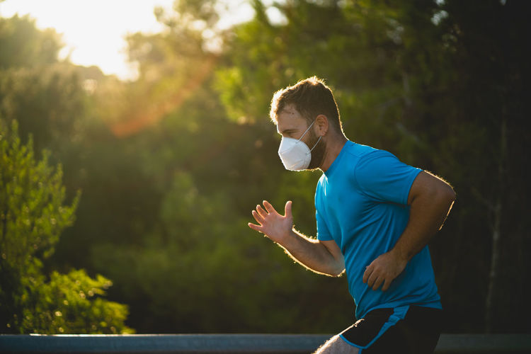 Side view of man wearing mask running against trees