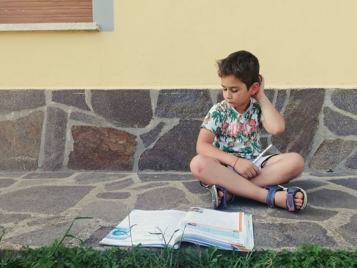 Girl sitting on book against wall