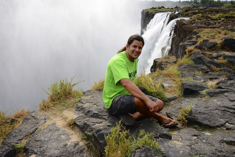 Man sitting on cliff against waterfall
