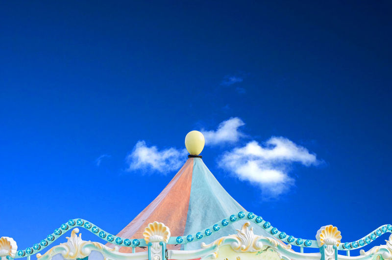 High section of carousel against blue sky