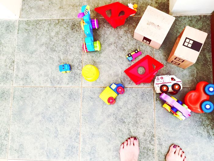 Cropped Legs Of Woman Standing By Toys On Floor