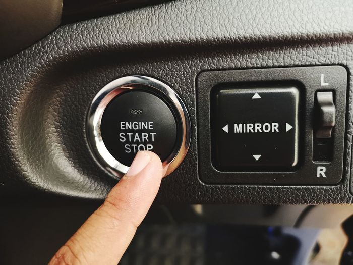 Close-up of hand pushing start button in car
