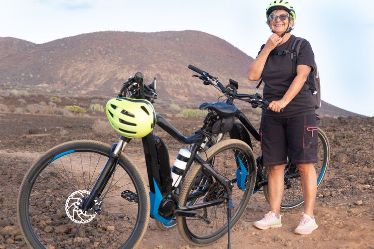 Full length of woman standing by bicycle on land