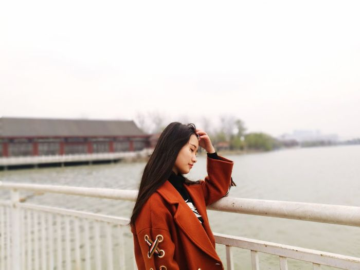 Side view of young woman with eyes closed standing by railing against lake