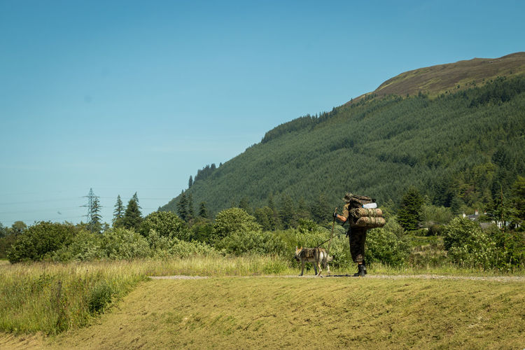 mountaineer and his dog Mountaineer Dog Saddlebag Hiking Adventure Scotland Highlands Forest Outdoors Tree Clear Sky Men Agriculture Togetherness Field Sky Woods Canine Hiker Hiking Pole Mountain Climbing Siberian Husky Camouflage Clothing Agricultural Field Cultivated Land