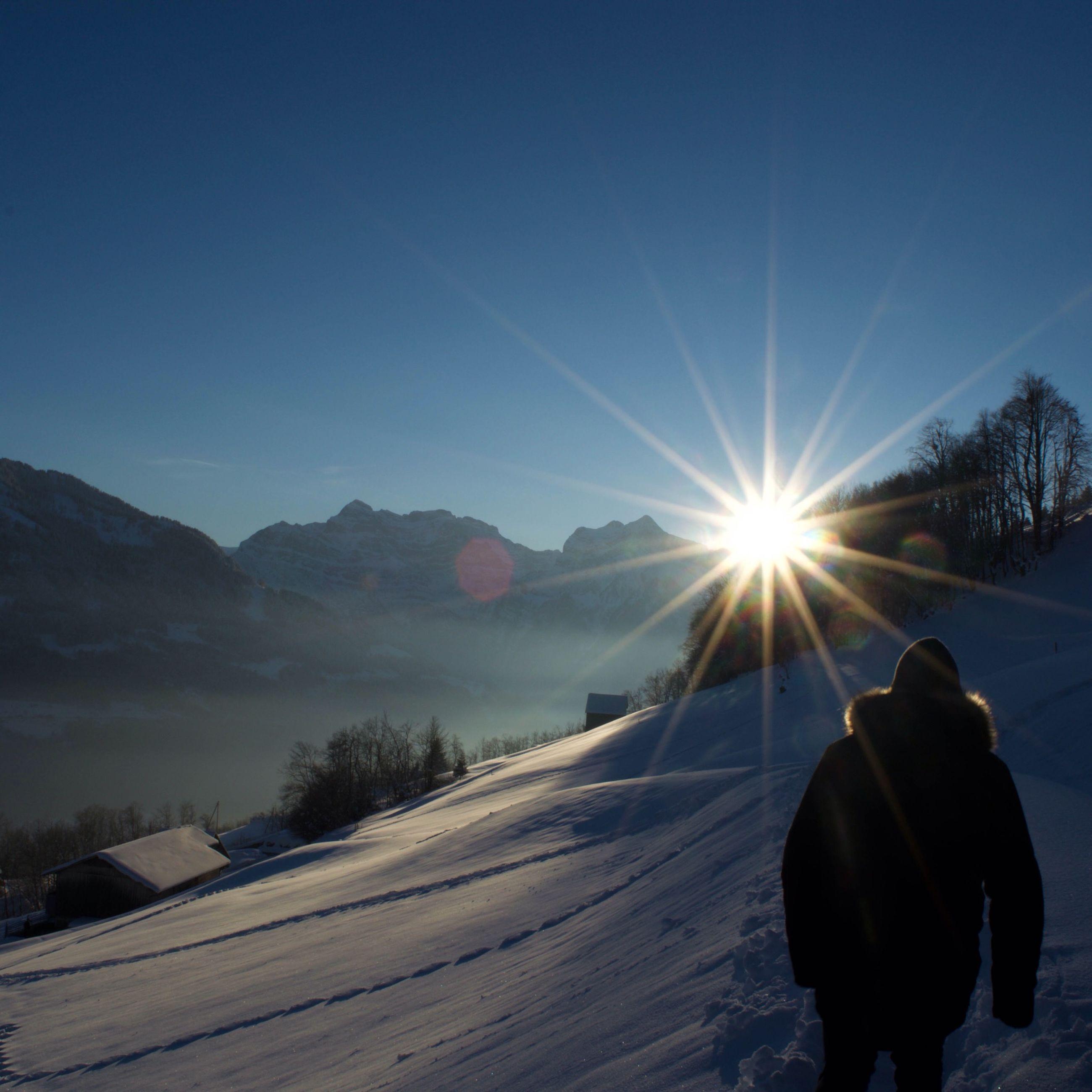 sun, sunlight, sunbeam, clear sky, lens flare, snow, winter, men, sky, cold temperature, lifestyles, leisure activity, mountain, transportation, blue, copy space, rear view, silhouette