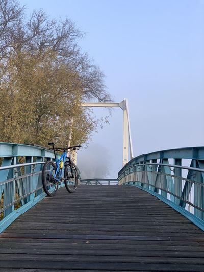 Bicycle on footbridge against sky
