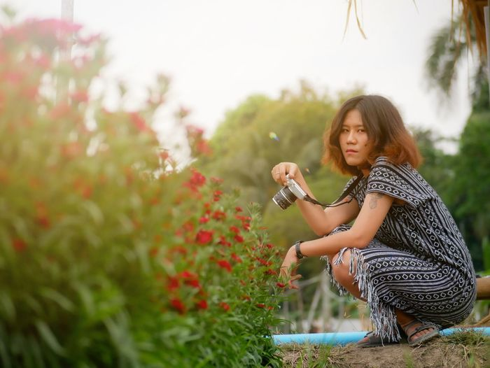 Young woman sitting on pink flowering plant