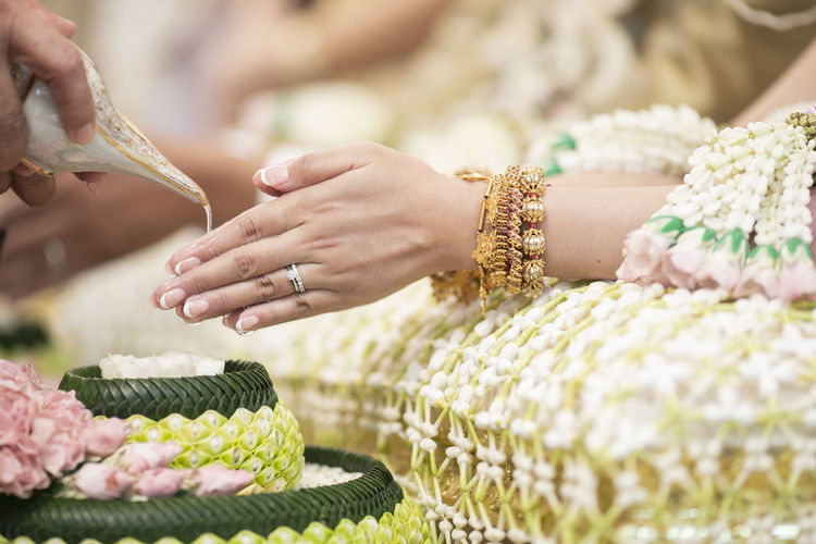 Cropped Hand Pouring Water With Shell On Bride Hands During Wedding Ceremony